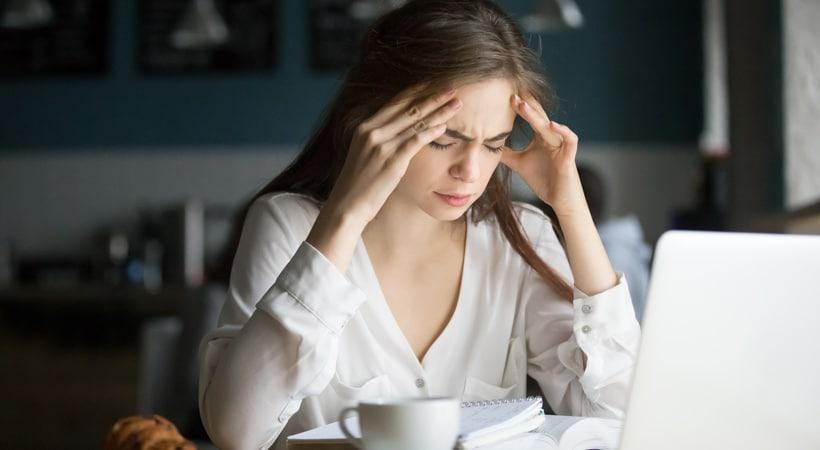Nervous stressed female student feeling headache studying